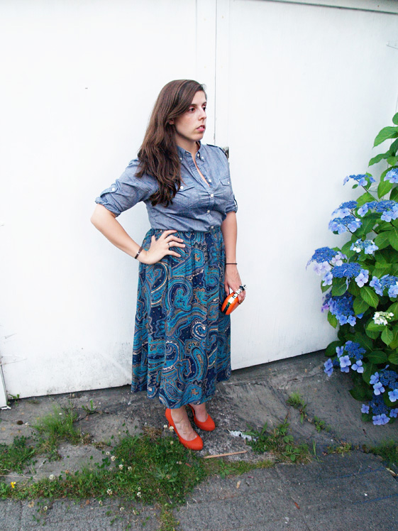 blue paisley mid length skirt, chambray shirt, and orange pumps and clutch